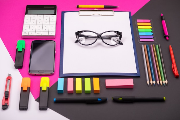 Картина современного художественного пространства с буфером обмена, очки, канцелярские принадлежности и смартфон на розовый и черный