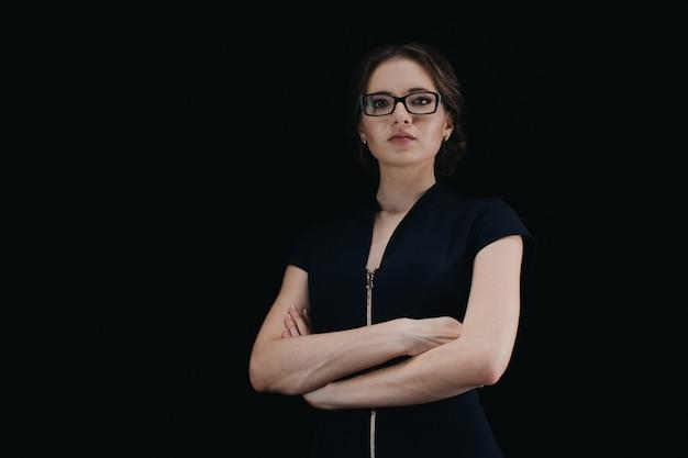 黒の組んだ腕を持つ魅力的な若い白人女性の肖像画