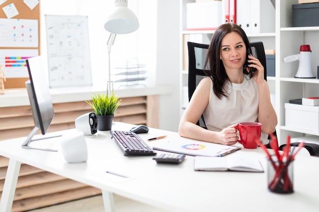 コンピューターデスクのオフィスに座って、電話で話し、赤いカップを保持している若い女の子。