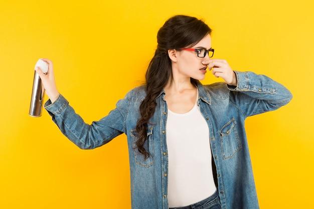 不快な臭いに対する噴霧器を持つ若い女性