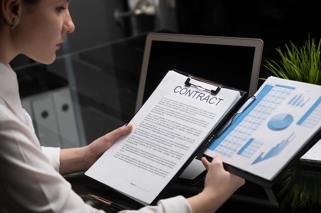 Молодая девушка держит контракт и фирму статистики
