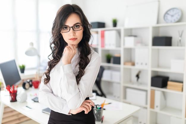 Красивая молодая девушка опирается рукой на подбородок и стоит возле офисного стола.