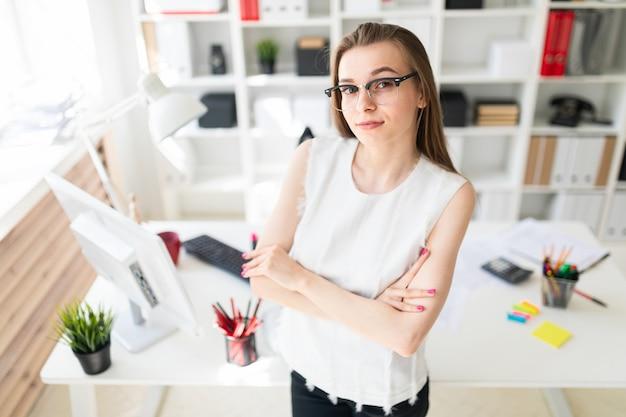 Красивая молодая девушка в офисе стоит возле стола.