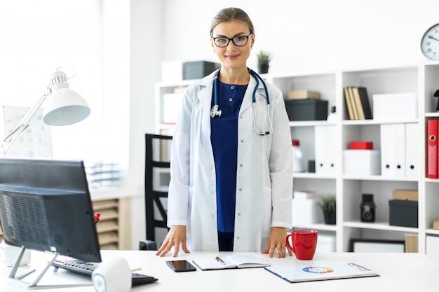 Молодая девушка в белом халате стоит возле стола в своем кабинете.
