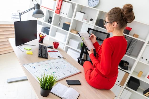 若い女の子は彼女のオフィスのテーブルの上に座って、彼女の手で鉛筆と書類を持っていました