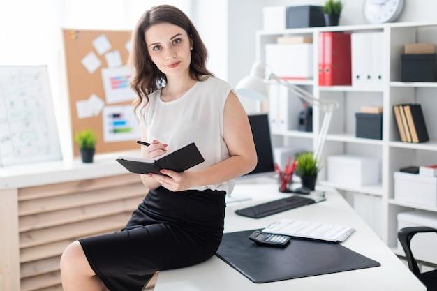 テーブルの近くのオフィスに立って、ペンとノートを保持している若い女の子。