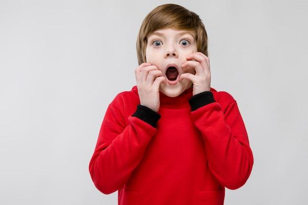 灰色の口を開けてかわいい困惑したびっくりした少年