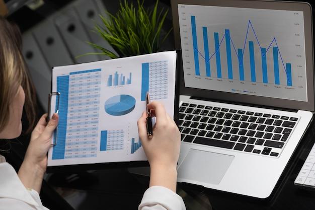 Бизнесмен, анализируя инвестиционные графики с ноутбуком. учет