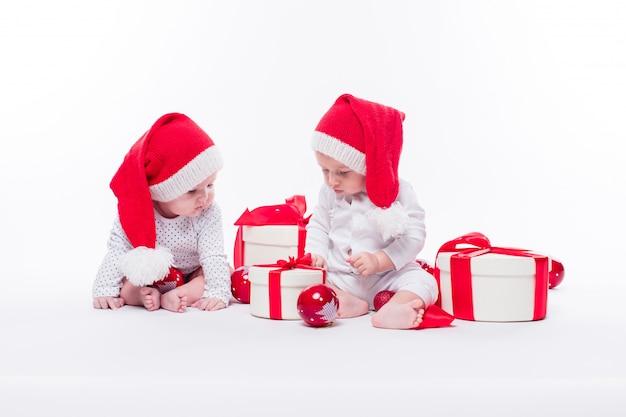 Два красивых малыша в новогодней шапке и белом теле сидят