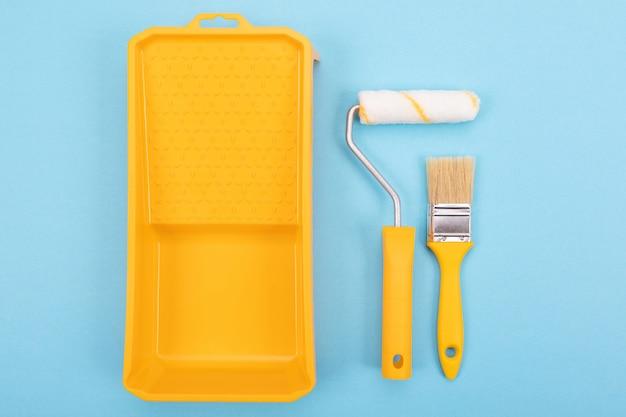 Инструменты рисования. кисть и валик с лотком для краски. макет