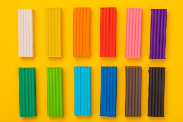 Набор красочных пластилина, изолированных на желтом фоне