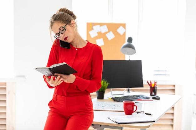 Молодая девушка стоит, опираясь на стол, держит ноутбук и разговаривает по телефону.