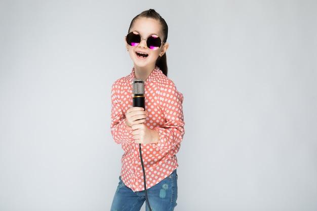 Девушка в оранжевой рубашке, очках и синих джинсах на сером фоне.