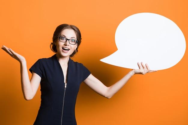 Портрет уверенно возбужденных красивая молодая деловая женщина с пузырем речи в руках, стоя на оранжевом фоне