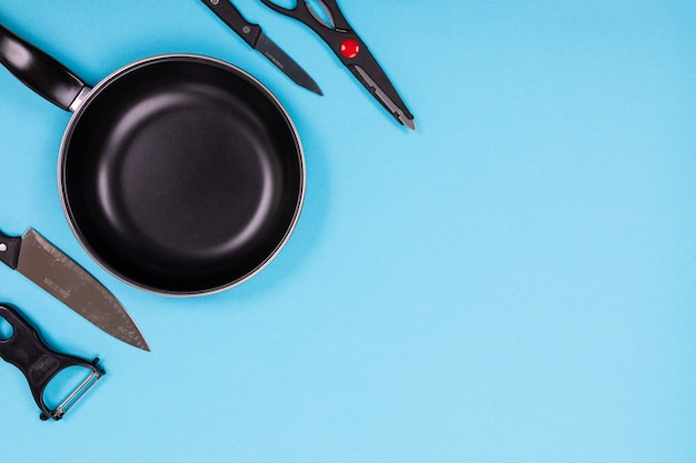 Крупным планом картина группы кухонной утвари на синем