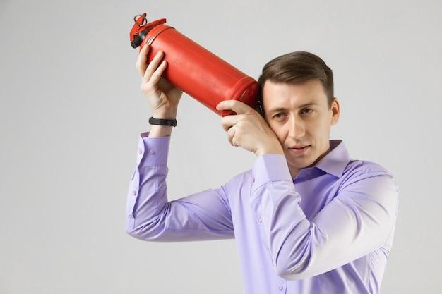 若い男が光の彼の頭に消火器を置く