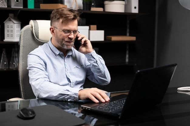 Серьезный бизнесмен работает на ноутбуке и разговаривает по мобильному телефону