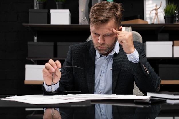 Бизнесмен сидит за компьютерным столом и думает о документах