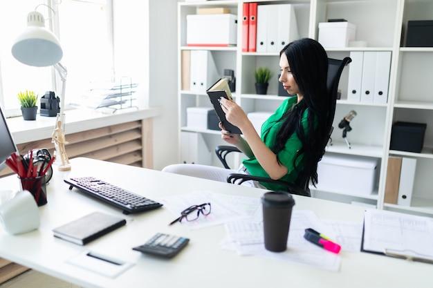 Молодая девушка сидит на рабочий стол и держит книгу.