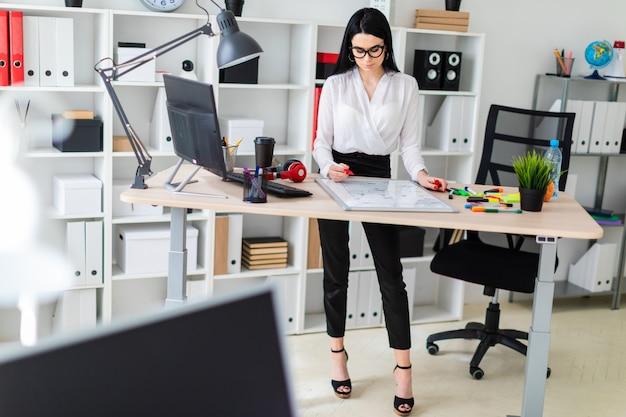 Молодая девушка стоит возле компьютерного стола и рисует маркер на магнитной доске.