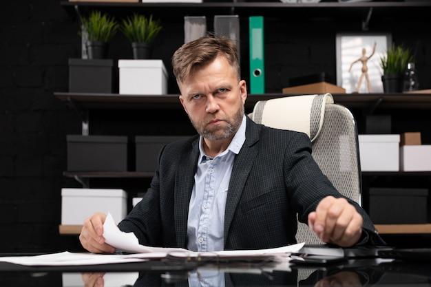 Бизнесмен сидит за столом компьютера и слезы документ