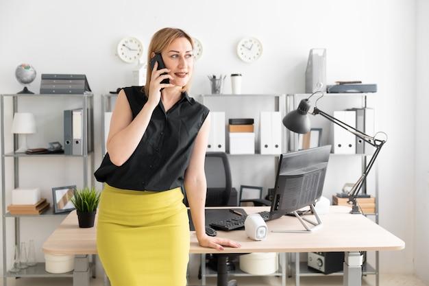 Молодая девушка, стоя в офисе и разговаривает по телефону.