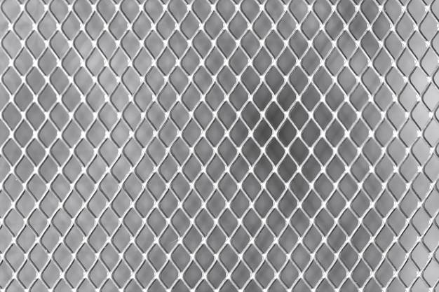 Квадратная сетка на белой стене металла крупным планом