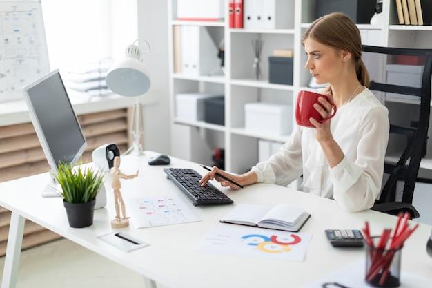 若い女の子がオフィスのテーブルに座って、赤カップを手に持ってコンピューターで働いています。