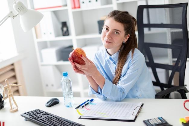 Молодая девушка сидит за столом в офисе и держит в руке яблоко.