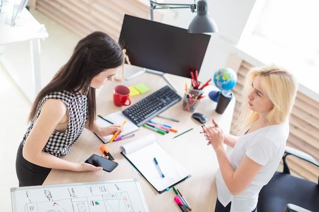 Две девушки работают в офисе. девушка держит телефон.