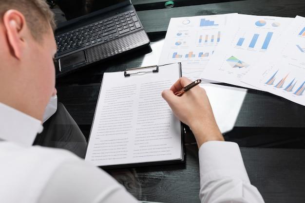 Молодой человек подписывает страхование в ярком офисе