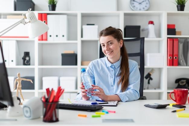 Молодая девушка сидит за столом в офисе и держит бутылку воды в руке.