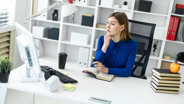 若い女の子がコンピューターの机に座っていると彼女の手に黄色のマーカーを保持しています。