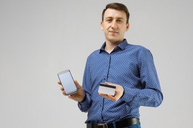銀行カードと携帯電話スタンドを持つ若者