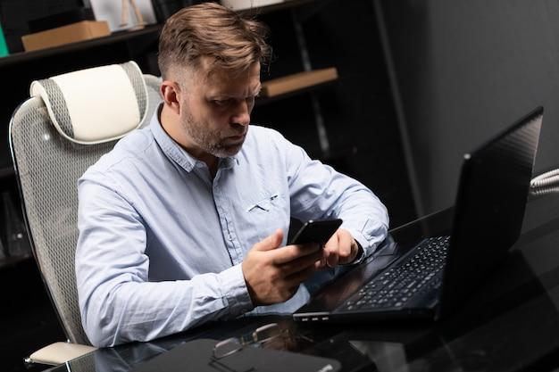 Бизнесмен сидит за столом компьютера и смотрит на телефон
