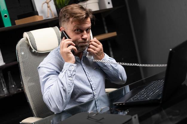 Молодой человек сидит за компьютерным столом и держит стационарный телефон и мобильный телефон