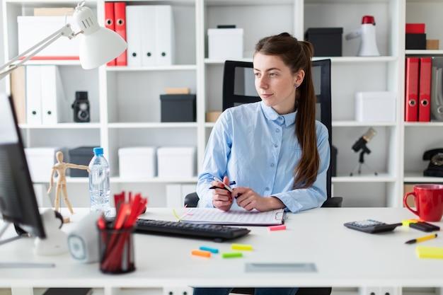 Молодая девушка сидит за столом в офисе, держит ручку в руке и работает