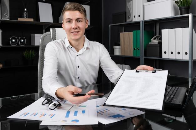 Молодой человек предлагает подписать страховку, сидя за столом в ярком офисе