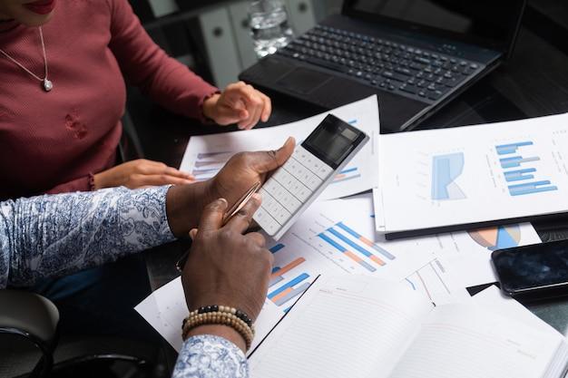 浅黒い肌の人々の手は、ビジネス空間のクローズアップで財務書類に対して電卓を保持します。