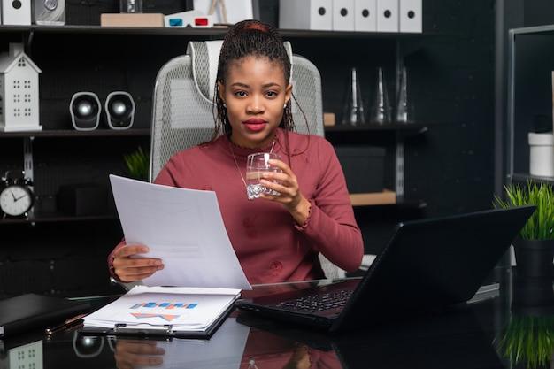 美しい若いアフリカ系アメリカ人実業家の水のガラスを保持し、オフィスのテーブルでドキュメントを操作