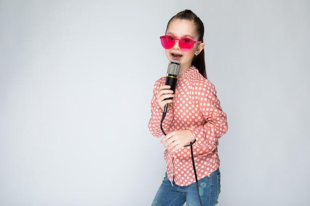 オレンジ色のシャツ、メガネ、グレーにブルージーンズの女の子。