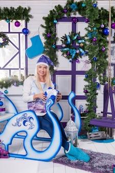 座っているサンタクロースの青いクリスマス帽子でセクシーなブロンド