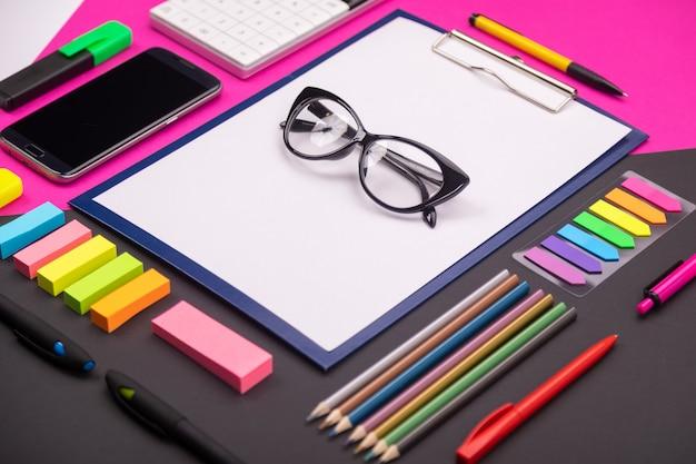 ピンクと黒のクリップボード、メガネ、文房具、スマートフォンを備えたモダンなアートスペースの写真。フラットレイアウトスタイル
