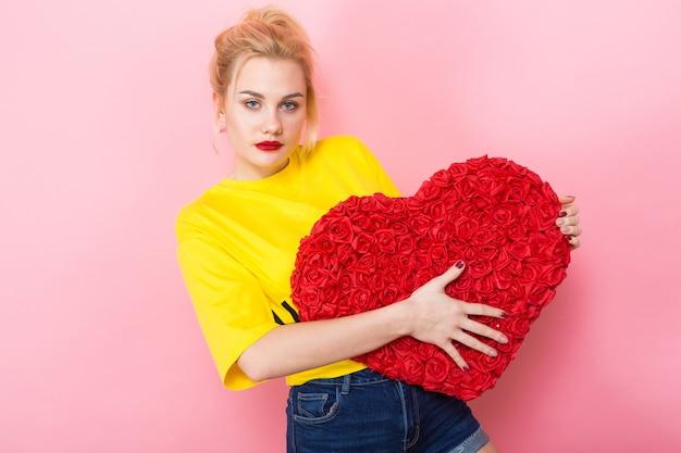 Привлекательная женщина держит большой красный цветок сердца