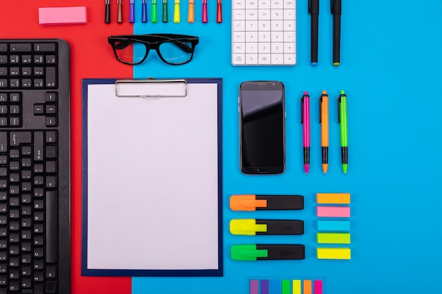 スマートフォン、クリップボード、ステッカー、およびカラフルな青と赤のペンでビジネスデスクのフラットレイアウト構成