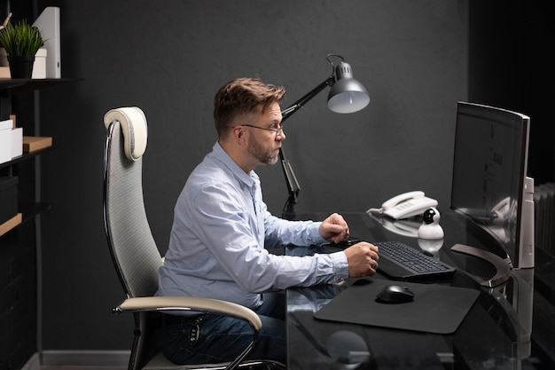 Деловой человек сидит в офисе за компьютерным столом и смотрит на монитор