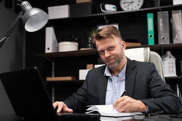 Молодой человек в деловой одежде, работа с ноутбуком и дневник