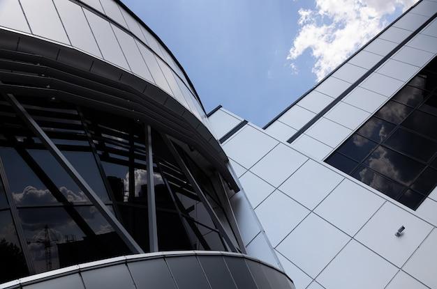 Вид снизу фрагментов современного здания с черными тонированными окнами на фоне неба