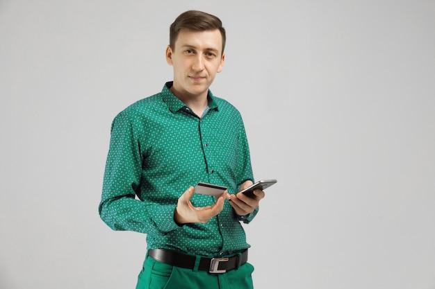 Молодой человек с банковской картой и мобильным телефоном стоит
