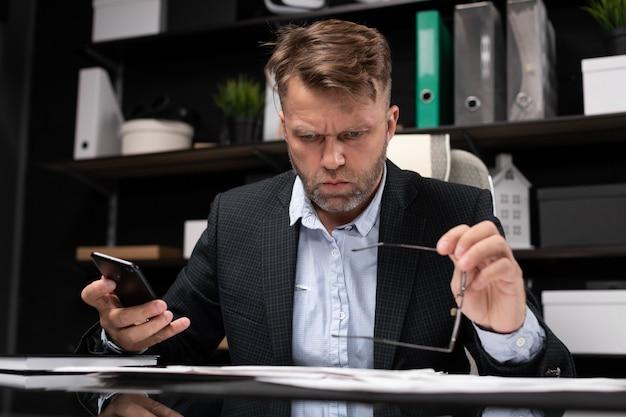 Бизнесмен сидит за компьютерным столом с телефоном в руках и думает о документах